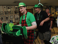NWA Democrat-Gazette/FLIP PUTTHOFF <br /> ST. PATS AT ST. ANDREWS<br /> James Crews (from left) and Don Schuler pass out St. Patrick's Day hats during the annual St. Patrick's Day dinner Saturday March 12, 2016 at St. Andrew's Episcopal Church in Rogers. The church men's group cooks the main course of corned beef and cabbage and women of the church bring desserts. The St. Patrick's Day meal has been a tradition at the church for years, the cooks said.