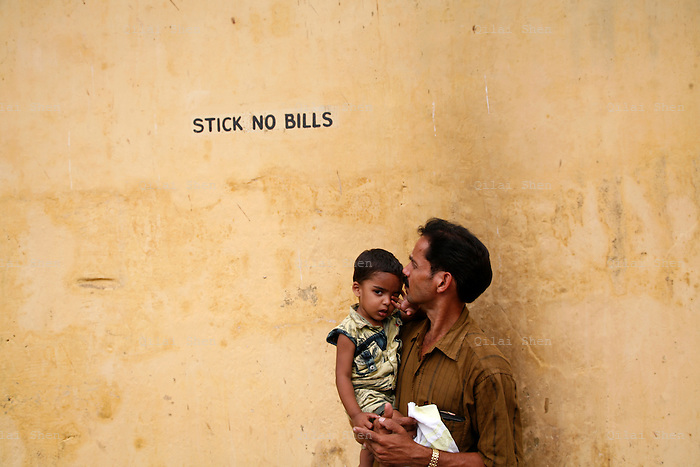 A man holds his baby while standing beside a wall in Kochi (formerly known as Cochin), India on Sunday, 28 January 2007.