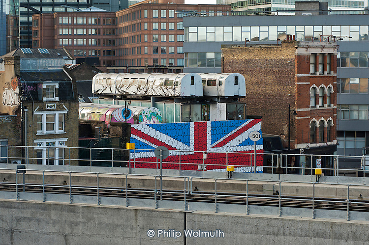 Recycled Jubilee line train carriages and shipping containers used as creative studios, on the roof of Village Underground, a renovated warehouse which also houses a non-profit gallery and club space in Shoreditch, London, a run-down commercial district  also known as Silicon Roundabout, which is undergoing gentrification as it becomes a centre for web-based companies and IT start-ups.