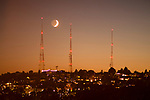 TV towers silhouetted at sunset with crescent moon setting over Queen Anne Hill