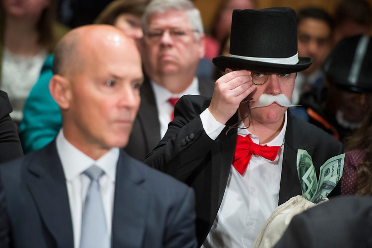 UNITED STATES - OCTOBER 04: Amanda Werner, who is dressed as Monopoly's Rich Uncle Pennybags, sits behind Richard Smith, left, CEO of Equifax, during a Senate Banking, Housing and Urban Affairs Committee hearing in Dirksen on the company's security breach on October 4, 2017.  (Photo By Tom Williams/CQ Roll Call)