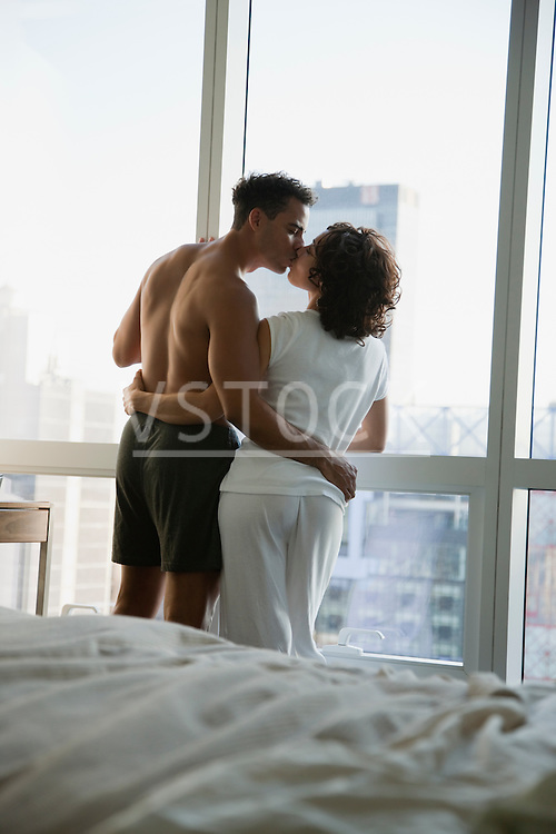 USA, New York City, couple kissing by window in bedroom