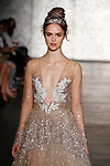 Model walks runway in a long sleeve V neck sequined golden tulle ballgown, from Inbal Dror Fall 2018 bridal collection on October 5, 2017; during New York Bridal Fashion Week.