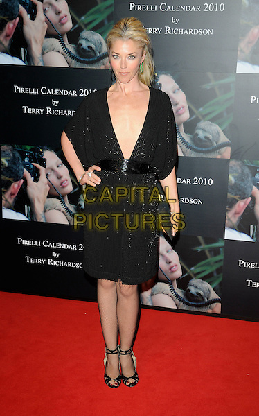 TAMARA BECKWITH .At the 2010 Pirelli Calendar Cocktail Reception and Gala Dinner, Old Billingsgate Market, London, England, UK, November 19th 2009..full length black dress hand on hip low cut plunging neckline sparkly ankle strap open toe shoes clutch bag cut out v-neck waistband kimono sleeve cleavage .CAP/CAN.©Can Nguyen/Capital Pictures.