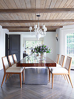 In the dining room, the circa-1960 burl-top table is by Milo Baughman, and vintage T.H. Robsjohn-Gibbings chairs are covered in a Romo fabric; the plaster chandelier is from the 1930s, and the oak flooring has been finished with a custom stain.