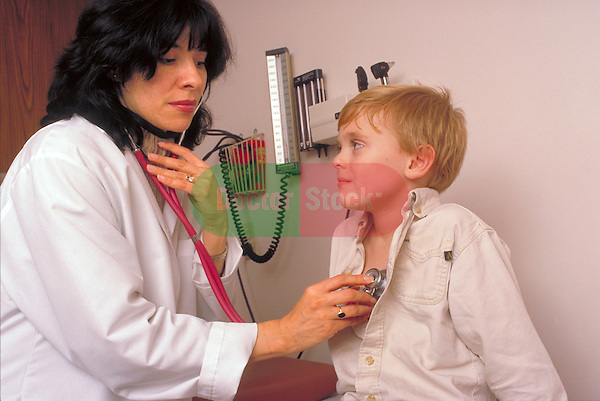 woman doctor examines heart of young boy