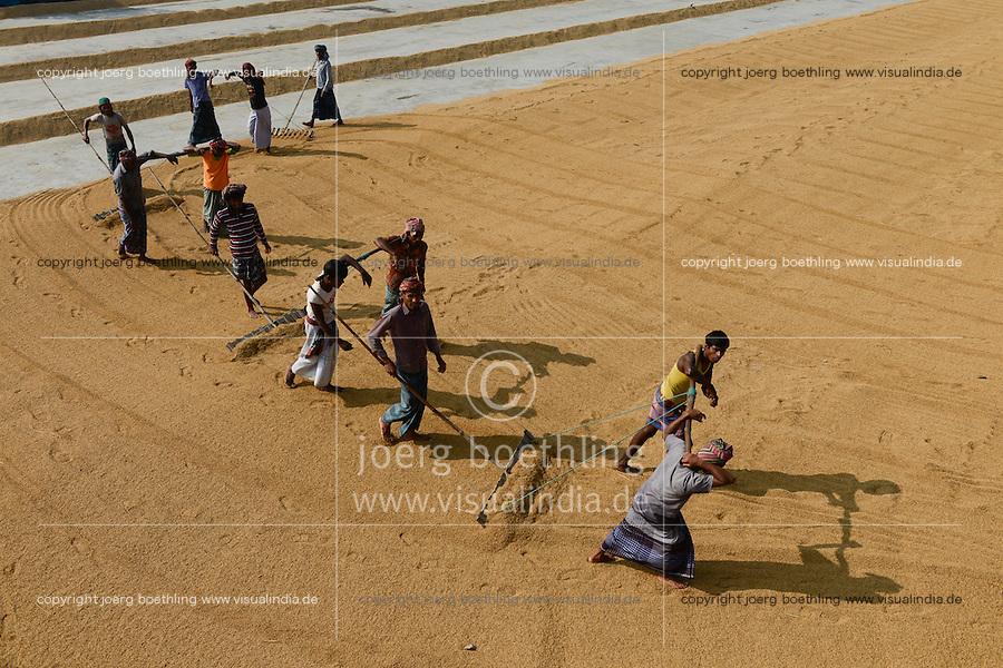 BANGLADESH Tangail, worker turn over paddy for drying in rice mill near Kalihati / BANGLADESCH Arbeiter wenden Reiskoerner zum Trocknen in einer Reismuehle