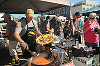 """NWA Democrat-Gazette/FLIP PUTTHOFF <br /> TREE CUISINE<br /> Jeff Pollock of Rogers adds smoked squirrel pieces to his team's dish Saturday Sept. 12 2015 during the third annual World Championship Squirrel Cookoff in downtown Bentonville. Teams of squirrel chefs prepared an array of dishes with squirrel meat, such as gumbo, meatballs and stuffed peppers. The team """"Bud and Bones"""" comprised of Jeff Terry of Pea Ridge, Dan Judd of Rogers and Tim Owens of Bella Vista won the cookoff with their dish, empanadas with spanish cream rice. Money raised at the event benefited Sheep Dog Impact Assistance, which aids military and law enforcement personnel, said Joe Wilson, cookoff chief."""