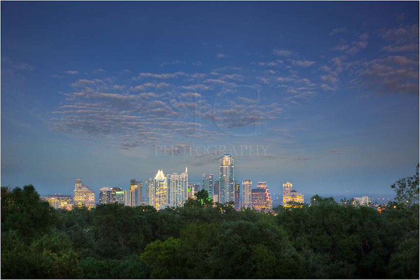 On a fading September evening, the Austin skyline begins to light up as the sun disappears behind me in the west. This Austin, Texas, Image is a blend of two images - one a longer exposure to give some color to the clouds overhead, and the other to give more definition to he details of the architecture and lights of downtown. <br />
