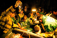 Emergency personnel attend a RTA in which the driver and front seat passenger remain trapped. The paramedic is attempting to find a vein in which to inject drugs. They have placed an oxygen mask and a neck brace on the victim. This image may only be used to portray the subject in a positive manner..©shoutpictures.com..john@shoutpictures.com