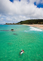 Couple swimming in Waimea Bay in their wedding attire
