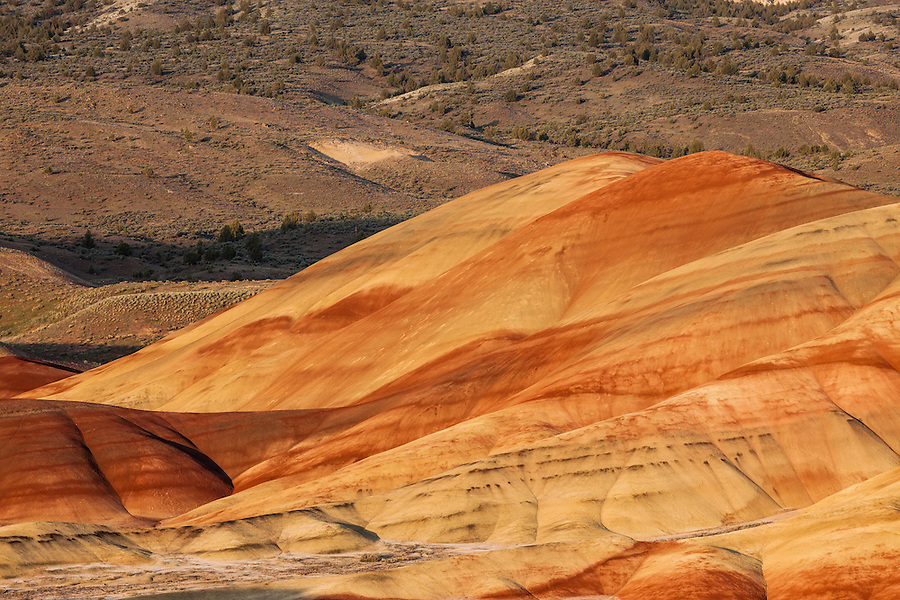 A red and yellow hill is lit by the setting sun in the Painted Hills section of the John Day Fossil Beds National Monument in Wheeler County, Oregon.