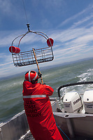 A USCG Auxiliary member aboard the patrol vessel Silver Charm captures a rescue basket lowered from a helicopter with a grounding hook to remove static electricty before bringing the basket on board.