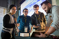 NWA Democrat-Gazette/CHARLIE KAIJO Julie Corona 17 of Rogers (from left), Jacob Zito 16 of Rogers and Julian Sanker 14 of Fayetteville look at an app that Chris Bader, constituent service representative, is showing, Thursday, March 15, 2018 at The Record in Bentonville. <br /> <br /> The nonprofit TeenDevConf in NWA gives grants to teens interested in learning about new technology. Its goal is to benefit &ldquo;hatchling hackers&rdquo; so they can use their powers for good.<br /> <br /> Julian Sanker, a teen, started a fundraising campaign with a goal of funding enough for 15 students to attend a developer&rsquo;s conference for free. He&rsquo;s now raised enough for more than 25 students to attend. The Nowhere Developers Conference hosted speakers from Walmart, Google, MailChimp, among others.