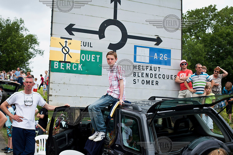 Local people stand in front of a road sign including a boy sitting on the roof of a car as they wait see the Tour de France cycling competition pass through their village.