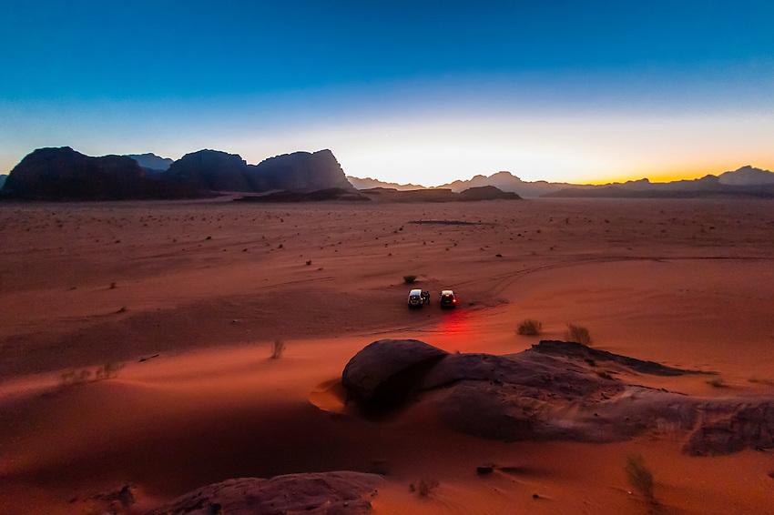 Vehicles stopped in the Arabian Desert to watch the sunset, Wadi Rum, Jordan.