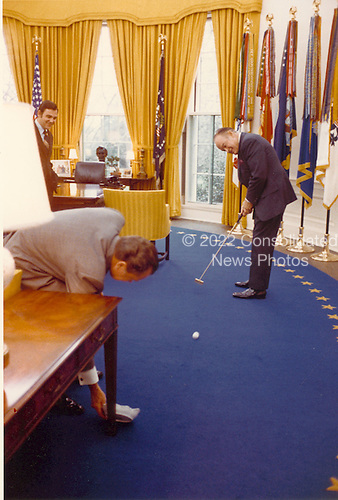 Entertainer Bob Hope shows off his putting to United States President Richard M. Nixon in the Oval Office at the White House in this photo dated 20 April, 1973.  Looking on at far left is White House Press Secretary Ron Ziegler..Credit: White House via CNP