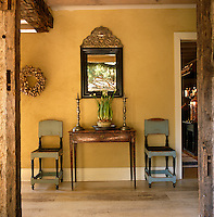 A pair of rustic wooden chairs flank a console table and a Swedish Baroque mirror in the yellow painted hallway