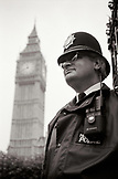 ENGLAND, London, a bobby stands below Big Ben, the great clock at the north end of the Palace of Westminster (B&W)