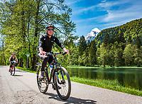 Deutschland, Bayern, Berchtesgadener Land, Bischofswiesen, Ortsteil Boecklweiher: mit dem Mountainbike am Boecklweiher entlang, im Hintergrund die schneebedeckten Gipfel des Watzmann in den Berchtesgadener Alpen   Germany, Upper Bavaria, Berchtesgadener Land, Bischofswiesen, district Boecklweiher: mountainbiking alongside lake Boecklweiher, at background snowcapped summits of Watzmann mountain range in the Berchtesgaden Alps