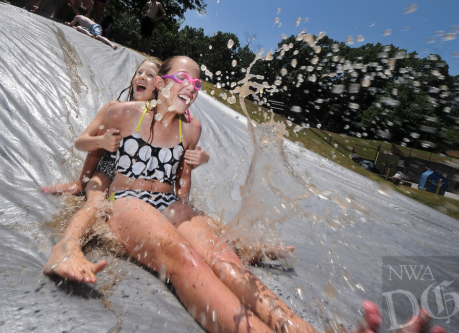 STAFF PHOTO BEN GOFF  @NWABenGoff -- 07/25/14 Lexi Cannady, 12, right, and Susanna Kelly, 8, both of Bella Vista, make a splash while slide down a wet tarp during the final day of Camp Bella Vista at Riordan Hall in Bella Vista on Friday July 25, 2014. The Bella Vista Property Owners Association camp for ages 7-12 included arts and crafts and swimming on Mondays and a variety of games and activities on Wednesdays and Fridays throughout June and July.