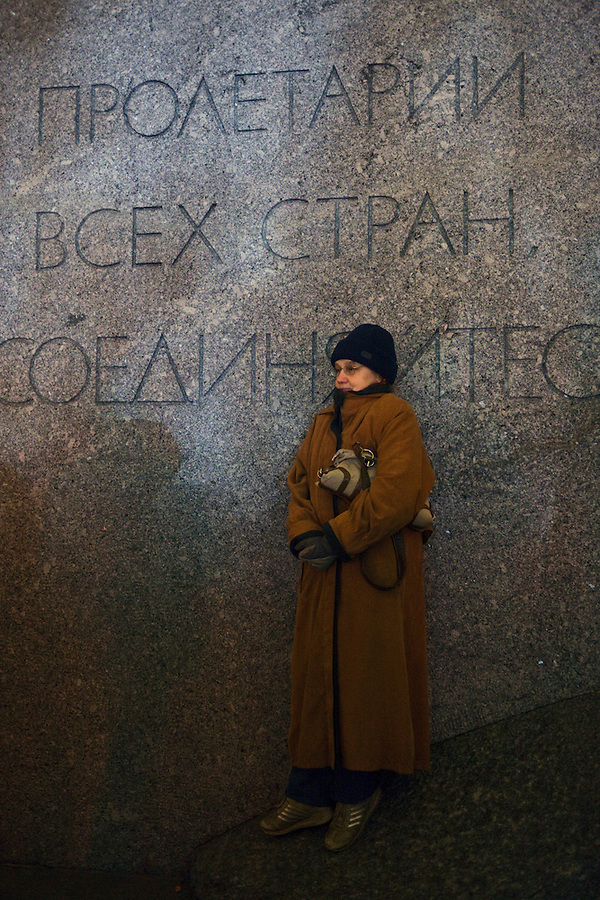 """Moscow, Russia, 28/10/2011..A woman watching the gala reopening of the Bolshoi Theatre on a giant video screen while standing on the plinth of a statue of Karl Marx with the inscription """"Workers of the world unite"""". The theatre had been closed since 2005 for reconstruction work that cost some $700 million."""