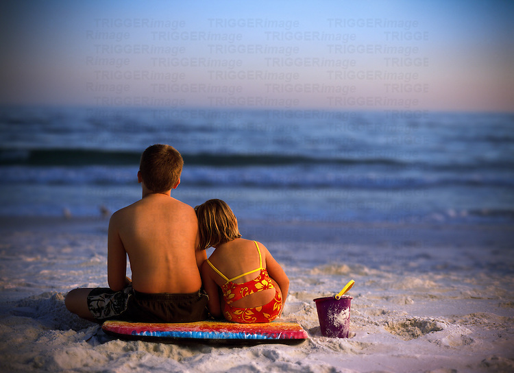 A brother and sister sit together on a boogie board and watch the ocean on a beach in Florida