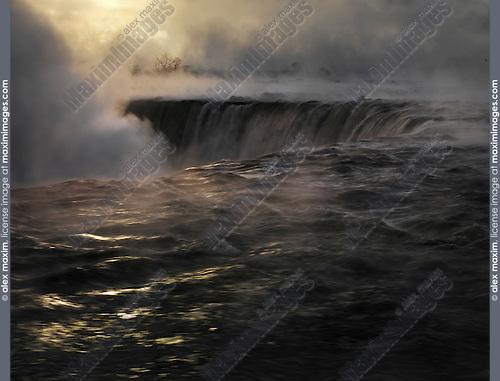 Niagara Falls covered in mist, beautiful dramatic mysterious dark sunrise scenery, wintertime scenic. Niagara Falls, Ontario, Canada.