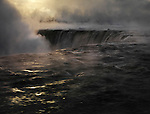 Niagara Falls covered in mist, beautiful dramatic mysterious dark sunrise scenery, wintertime scenic. Niagara Falls, Ontario, Canada.