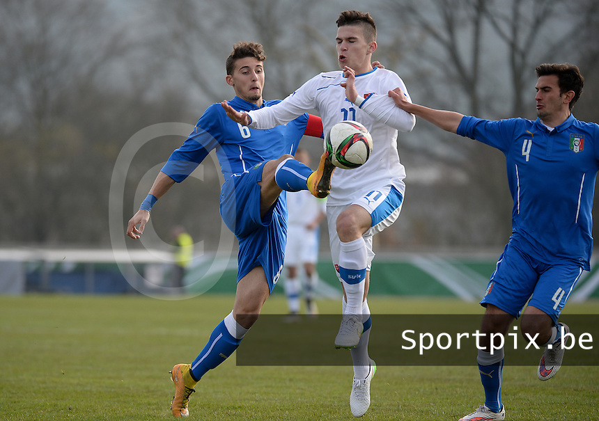 20150323 - MARBURG , GERMANY  :  Italian Andres Llamas Acuna (left) pictured clearing the ball in front of Slovakian Lubomir Tupta (11) and teammate Italian Alessandro Mattioli (right) during the soccer match between Under 17 teams of Slovakia and Italy , on the second matchday in group 8 of the UEFA Elite Round Under 17 at Georg-Gassmann , Marburg Germany . Monday 23 rd  March 2015 . PHOTO DAVID CATRY
