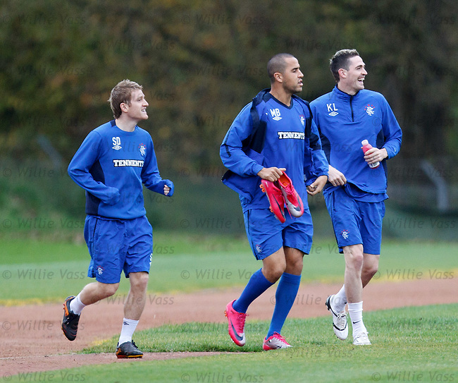 Madjid Bougherra laughs as he carries a spare pair of pink shoes to training with Kyle Lafferty and Steven Davis