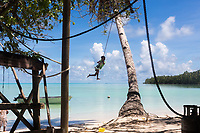 """""""Unless the global community steps up our actions to significantly lower green house gas emissions...Tuvalu will dissapear completely within the next 30-50 years"""", said Tuvaluan Prime Minister Enele Sosene Sopoanga in his address to the United Nations General Assembly in 2017. As this young boy swung from a tree on one of Tuvalu's coral atoll islands, the danger and concern is not immediately evident but the slowly rising seas threaten this jewel in the Pacific.  Funafuti, Tuvalu. March, 2019."""