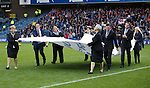 Armed forces parade at half-time, Rangers staff carry a banner around the park