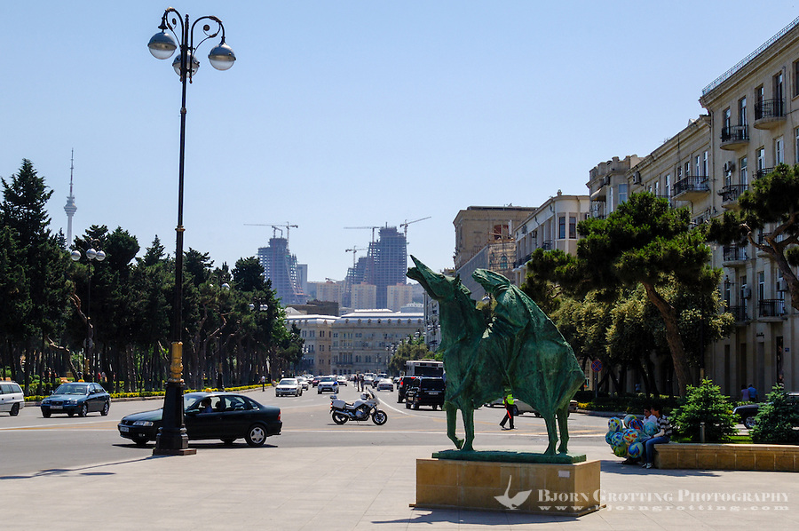 Azerbaijan, Baku. A statue in front of the Azerbaijan State Carpet Museum. Flame Towers, a residential complex under construction in the background.