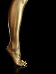 Woman legs covered with gold. Isolated on black background.