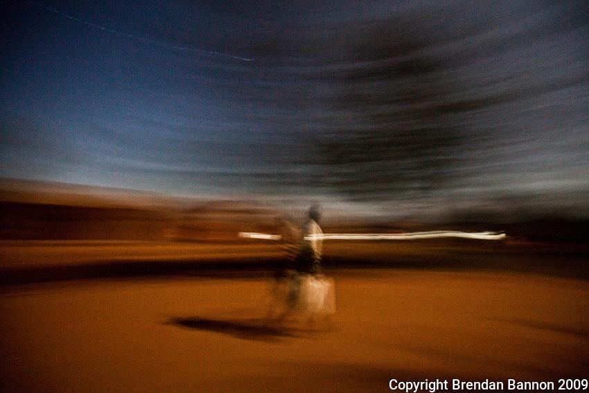 A woman walking under the moonlight in Madi Opei, Uganda.