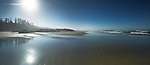 Surreal panoramic scenery of Pacific Rim National Park Long Beach sandy ocean shore during low tide in bright summer morning light. Tofino, Vancouver Island, BC, Canada.