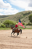 USA, Wyoming, Encampment, a young man rides his horse carrying the American flag, Abara Ranch