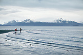 USA, Alaska, Homer, kids play by the edge of Kachemak Bay at Bishop Beach with the Kenai Mountains in the distance