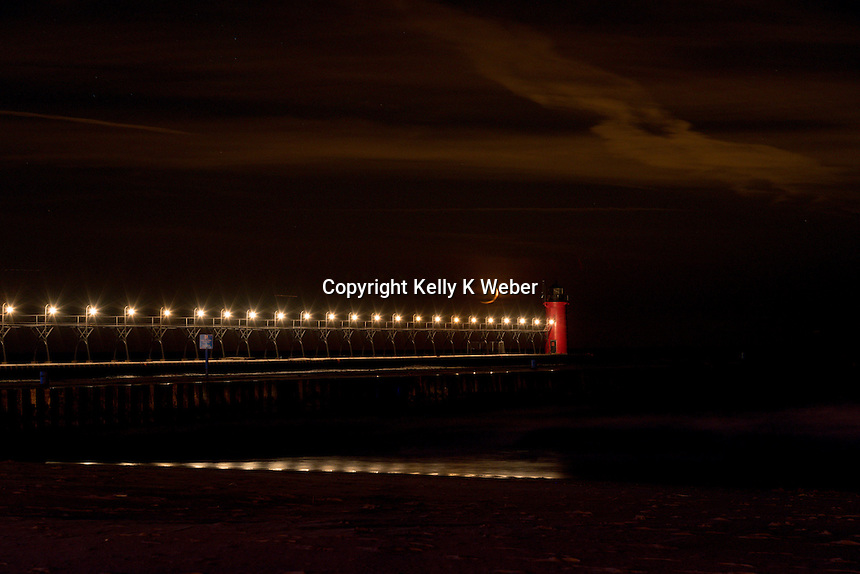 Crescent moon setting on Lake Michigan in South Haven, catwalk lights reflecting on the waters edge.
