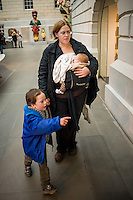 A mother breastfeeding her baby from a sling in a museum.<br /> <br /> London, England, UK<br /> 08/03/2015<br /> <br /> &copy; Paul Carter / wdiip.co.uk