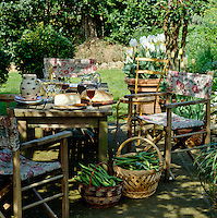 Director's chairs covered in a floral print surround a table laid for an informal lunch in the shade of an arbour