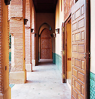 Large wooden doors open onto the covered walkway that encircles the inner courtyard