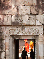 Buddhist monks and tourists walk through temples at Angkor, Siem Reap Province, Cambodia