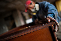 A carpentry worker polishes the chipboard case with a sandpaper machine at a table football workshop in Quito, Ecuador, 3 March 2012. Table football, also known as futbolin in Latin America, is a widely popular table-top game in Ecuador. During the annual fairs, the rusty old outdoor-designed tables, fully ocuppied by excited children, may be found on all public places, particularly on the squares and in the parks. Although there have always been several small table football workshops in all large Ecuadorean towns, the table football craft and tradition is on a decline in last years, mainly due to the video-game boom.