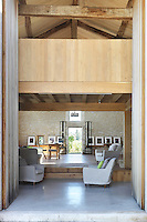 Vast barn doors open into the living area, its height divided by an elegant wood clad mezzanine designed by architect Jeremy Harris