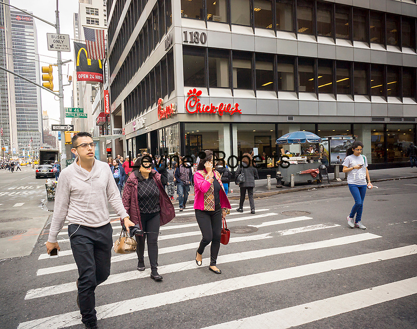 Crowds pass the new Chick-Fil-A fast food restaurant in New York on the day before its grand opening, Friday, April 1, 2016. The chain has a cult-like popularity with foodies extolling the virtues of their fried chicken sandwiches. (© Richard B. Levine)