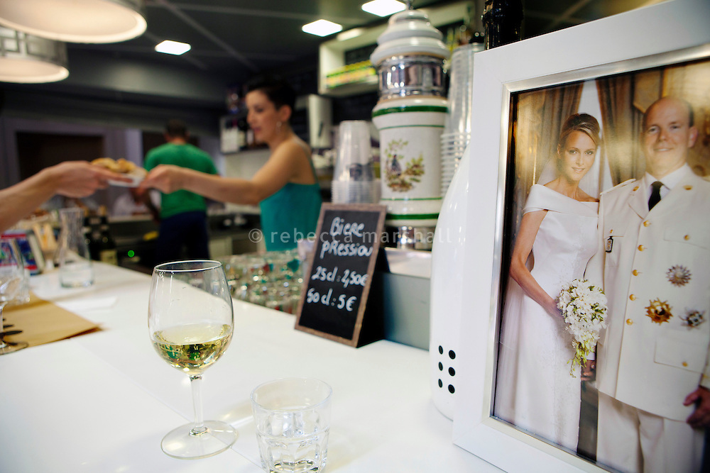 Framed official portraits of Monaco's prince and princess, Prince Albert II and Charlene, are displayed in shops, bars and other businesses across the principality. This one leans on the bar at café 'Le Comptoir', Le Nouveau Marché de la Condamine, Monaco, 5 July 2013