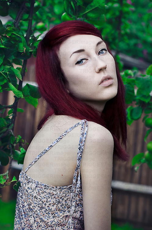 Young red-haired, blue-eyed and pale skinned female looking over her shoulder at the camera with apple tree and fence background.