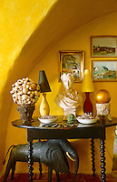 In an alcove of the salon a white marble bust placed on an antique table creates a pleasing contrast to the bright yellow walls